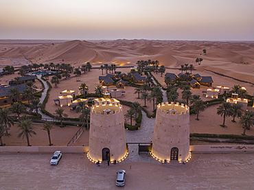 Aerial view from entrance to Arabian Nights Village desert resort amidst dunes at sunset, Arabian Nights Village, Razeen Area of Al Khatim, Abu Dhabi, United Arab Emirates, Middle East