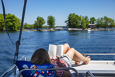 Young woman relaxes on the sundeck of a Le Boat Horizon houseboat and reads a book, Big Rideau Lake, Ontario, Canada, North America