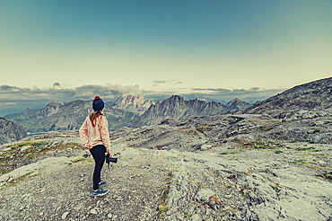 Woman with camera stands on a mountain near Lünersee, Vorarlberg, Austria, Europe