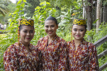 Three friendly women in traditional costume in the Sarawak Cultural Village, Kampung Budaya Sarawak, near Kuching, Sarawak, Borneo, Malaysia, Asia