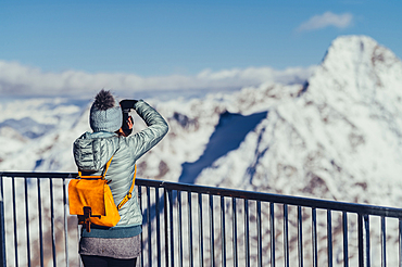 Woman with camera on the Corvatsch Glacier in the Engadin, Grisons, Switzerland, Europe