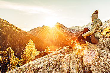 Woman sits on rocks in Maloja and enjoys the sunset, Engadin, Graubünden, Switzerland, Europe