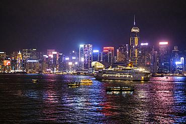Cruise ship Pisces in Victoria Harbor with city skyline at night, Hong Kong, Hong Kong, China, Asia