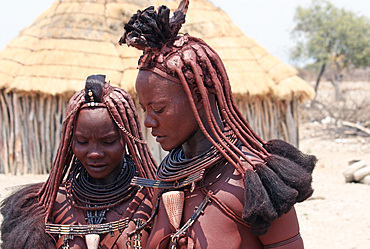 Angola; southern part of Namibe Province; two Muhimba women; traditional hair styling; Strands of hair stuck together with red earth and fluffy fur; Leather chokers; Skin tinted with red earth