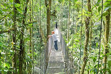 Man standing on hanging bridge, Arenal Volcano National Park, La Fortuna, Costa Rica