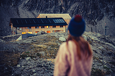 Woman stands during twilight at the Totalphütte in the Rätikon above the Lünersee, Vorarlberg, Austria, Europe