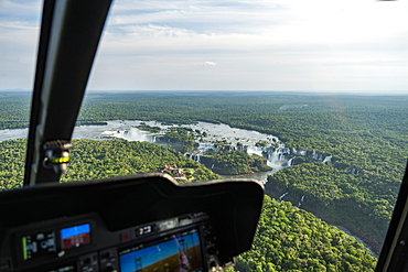 Aerial view of the waterfalls at Iguazu Falls seen through the window of a helicopter with cockpit instruments in the foreground, Iguazu National Park, Parana, Brazil, South America