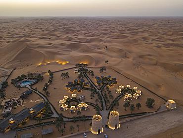Aerial view of Arabian Nights Village desert resort amid dunes at sunset, Arabian Nights Village, Razeen Area of Al Khatim, Abu Dhabi, United Arab Emirates, Middle East