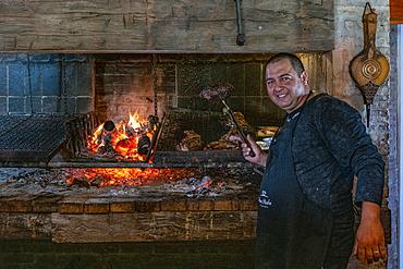Friendly cook prepares delicious asado meat on charcoal grill in Finca Piedra, San José de Mayo, Colonia Department, Uruguay, South America