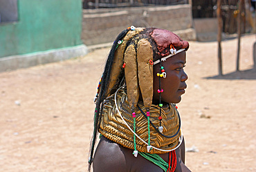Angola; Huila Province; small village near Chibia; young Muhila woman with typical neck and headdress; Tufts of hair covered with clay and fixed; massive choker made of woven straw and earth