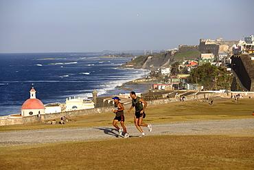 Two joggers at the park in front of castillo San Felipe del Morro, view over the north coast, San Juan, Puerto Rico, Carribean, America