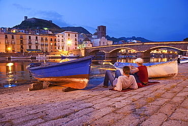Two at the banks of the river Fiume Temo at dusk, view to the Castello di Serravalle, Bosa, Sardinia, Italy, Europe