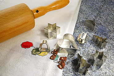 Cookie cutters for Christmas cookies and rolling pin laying on worktop