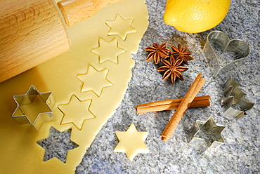 Stars cutted out of cookies dough, cookie cutters for Christmas cookies, rolling pin, lemon, cinnamon and star anise laying at worktop