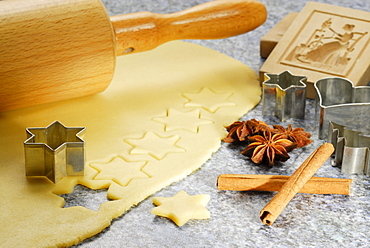 Stars cutted out of cookies dough, cookie cutters for Christmas cookies, rolling pin, wood pattern, cinnamon and star anise laying at worktop