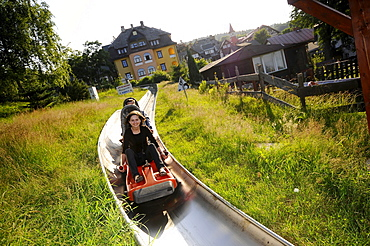 Tourists on the summer toboggan run in Karpacz, Bohemian mountains, Lower-Silesia, Poland, Europe