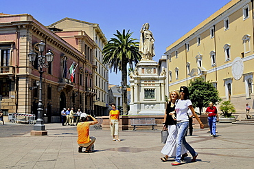 A monument and people on the sunlit Piazza Eleonora, Oristano, Sardinia, Italy, Europe