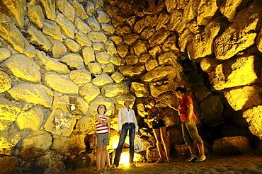 Tourists inside the illuminated Nuraghe Su Nuraxi at street of Nuraghi, South Sardinia, Italy, Europe