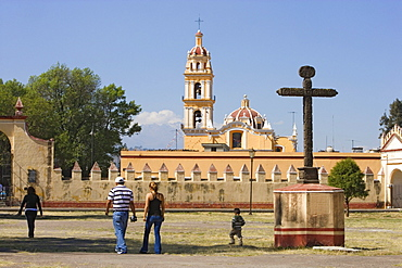 Family walking over the grounds of Ex-convento de San Gabriel in Cholula, the church of San Pedro is in the background, State of Puebla, Mexico