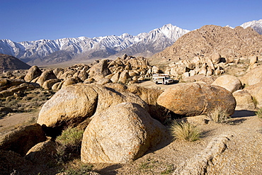 Vie at an American school bus in a rocky desert in front of snow covered mountains, Alabama Hills, Lonepine, California, USA