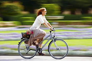 Mature woman riding bicyle, Munich, Bavaria, Germany