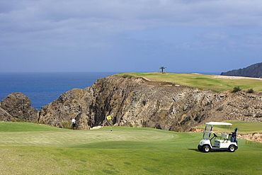 Golfer chipping ball from the green of Hole 15 at Porto Santo Golfe Golf Course, Porto Santo, near Madeira, Portugal