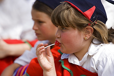Girl enjoying a lollipop during the Childrens Parade at the Madeira Flower Festival, Funchal, Madeira, Portugal