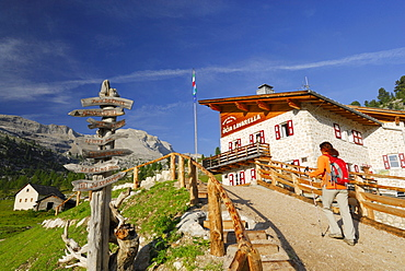 Woman arriving alpine hut Lavarella, Fanesalm, Naturpark Fanes-Sennes-Prags, Dolomites, Trentino-Alto Adige/South Tyrol, Italy