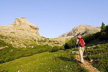 Woman hiking, Conturinesspitze and La Varella in background, Naturpark Fanes-Sennes-Prags, Dolomites, Trentino-Alto Adige/South Tyrol, Italy