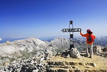 Woman summit cross of La Varella, Zehner and Neuner in background, Naturpark Fanes-Sennes-Prags, Dolomites, Trentino-Alto Adige/South Tyrol, Italy