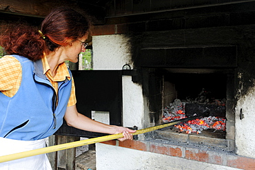 Woman removing burning charcoal from oven, Upper Bavaria, Bavaria, Germany