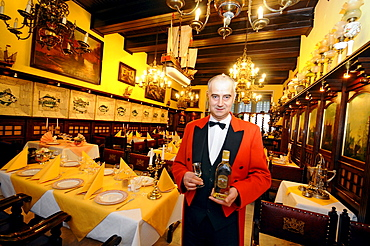 Waiter at the restaurant Pod Lososiem holding a bottle of gold water, Gdansk, Poland, Europe