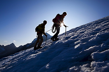 Two mountaineers ascending over icefield, Clariden, Canton of Uri, Switzerland