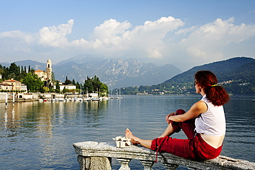 Woman enjoying view over Lake Como to Tremezzo, Lombardy, Italy