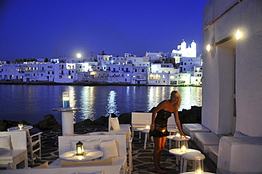 Woman at the terrace of a restaurant in the evening, Naoussa, island of Paros, the Cyclades, Greece, Europe