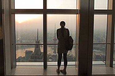 Woman looking from observation terrace of the World Trade Financial Centre at Shanghai city and Huangpu river at sunset, Pudong, Shanghai, China, Asia