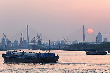 Ships on Huangpu River and cranes at the harbour at sunset, Pudong, Shanghai, China, Asia