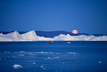 Full moon rising over icebergs from Ilulissat Kangerlua Icefjord at dusk, Ilulissat (Jakobshavn), Disko Bay, Kitaa, Greenland