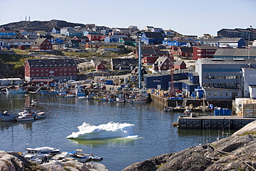 Iceberg at harbour with fishing boats and Royal Greenland Seafood Processing Plant, Ilulissat (Jakobshavn), Disko Bay, Kitaa, Greenland