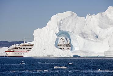 Cruise ship MS Deutschland and iceberg with hole from Ilulissat Kangerlua Icefjord, Ilulissat (Jakobshavn), Disko Bay, Kitaa, Greenland