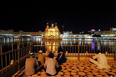 Golden Temple at night and praying Sikhs, Sikh holy place, Amritsar, Punjab, India, Asia