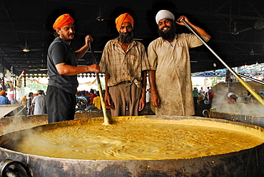 Golden Temple, three Sikh men with giant pot, free food for pilgrims, Sikh holy place, Amritsar, Punjab, India, Asia