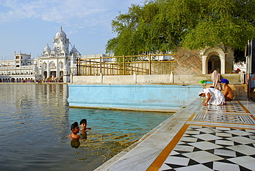 Golden Temple, two young Sikh men bathing in the holy lake, Sikh holy place, Amritsar, Punjab, India, Asia