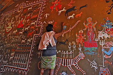 Man painting tribal art on a wall in a ceremonial hall, Bastar, Chhattisgarh, India, Asia