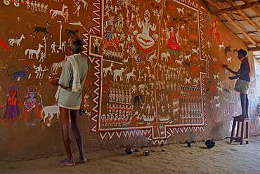 Men painting tribal art on a wall in a ceremonial hall, Bastar, Chhattisgarh, India, Asia