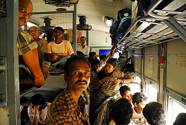 People in a train standing in the aile and sitting on the baggage rack, Orissa, India, Asia