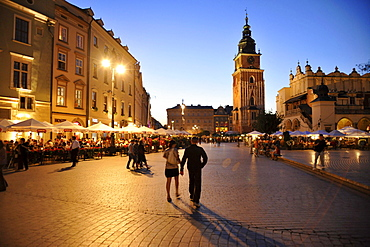 Rynek glowny, market place with street cafes and town hall tower at dusk, Krakow, Poland, Europe