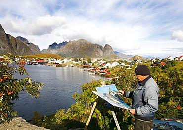 Norwegian painter in front of the coastal village Reine, Lofoten, Norway, Scandinavia, Europe