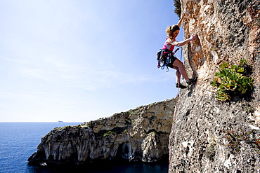 A young woman climbing on the cliffs at the bay of Zurrieq, Malta, Europe