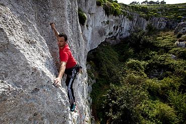 A young man climbing at Mgarr Ix-Xini rocks, Flakeout Walls, Gozo, Malta, Europe